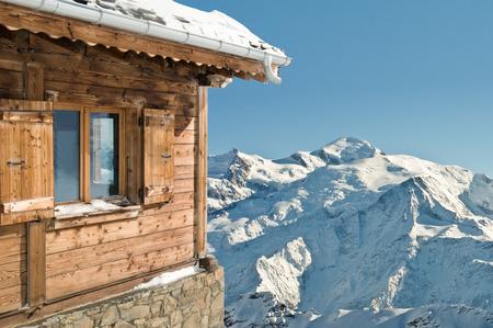 コテージから雪に覆われた montainand 青い空観します。 写真素材