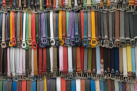 suede belt: muchos cinturones de cuero de colores en un mercado