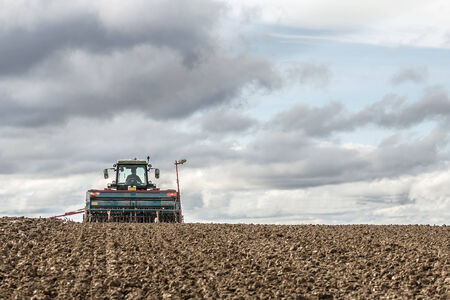 tractor seeding in a field on cloudy sky background photo