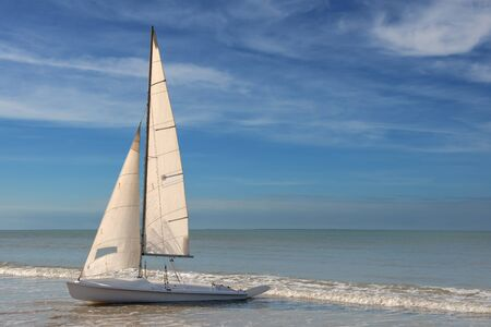 grounded: little white sailboat grounded on a beach on blue cloudy background