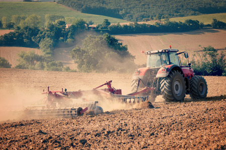 plough land: tractor and stubble plough in an harvested field vintrage filtered image Stock Photo