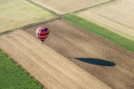balloons: Aerial view of an hot air balloon and its shadow nearly grounded over fields Stock Photo