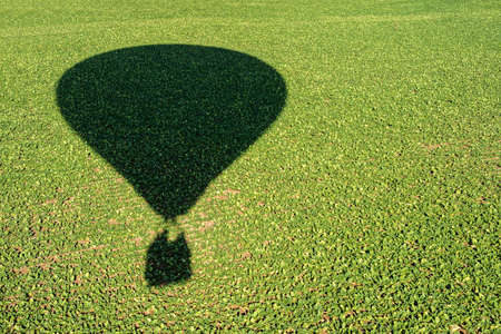 cultivated land: shadow of an hot air balloon flying over a cultivated land