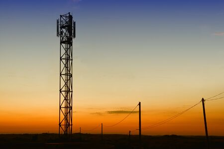 communication industry: gsm tower and old telephone pylons silhouettes at dusk