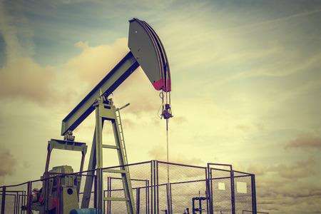 pozo petrolero: bombeo de la plataforma petrolera en el fondo del cielo nublado