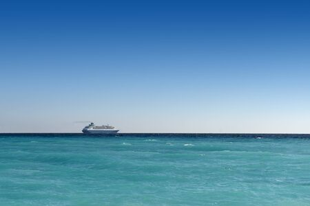 lifeboats: cruise liner sailing away on turquoise water and blue sky backround