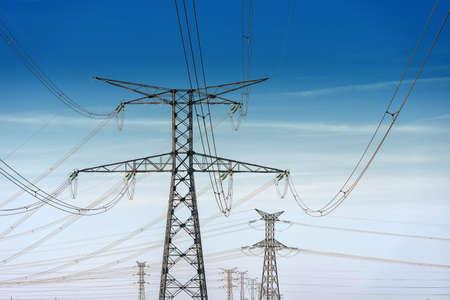torres el�ctricas: torres de alta tensi�n en el fondo azul cielo nublado Foto de archivo