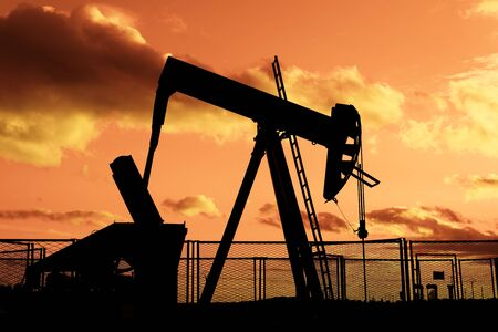 brent: oil rig pumping on cloudy sky background at dusk