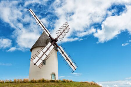 restored: ancient european windmill restored on the top of a hill Stock Photo