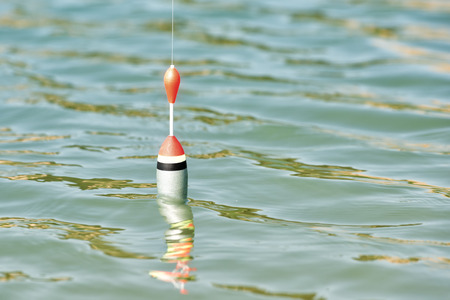 fishing cork floating on water surface Stock Photo
