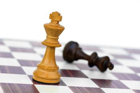 game over: white chess king check black on chessboard Stock Photo