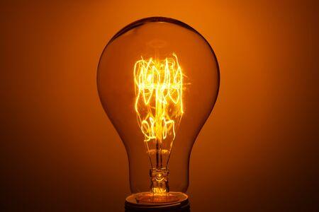 lighted vintage incandescent bulb on orange background