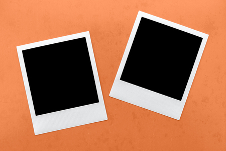 old photograph: two blank instant camera film frames on orange background.
