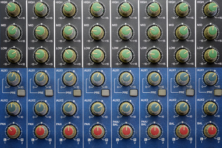 equalization and pan knobs on blue audio mixing table