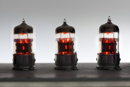 three orange vintage lighted amplifier tubes Stock fotó