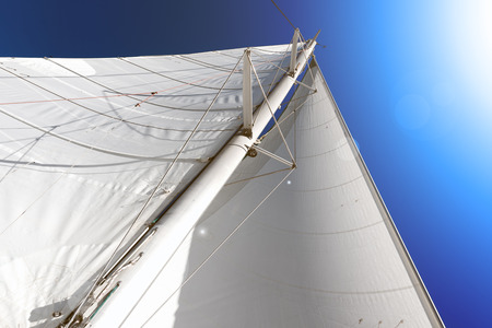 mainsail on board of a catamaran , blue ssky background Imagens