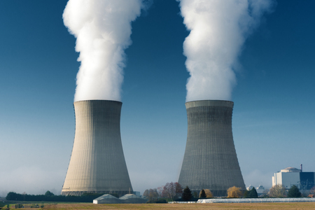 two power plant cooling towers steaming on dark blue sky background