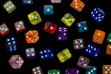 many falling translucent  multicolored  dices with white dots on black background