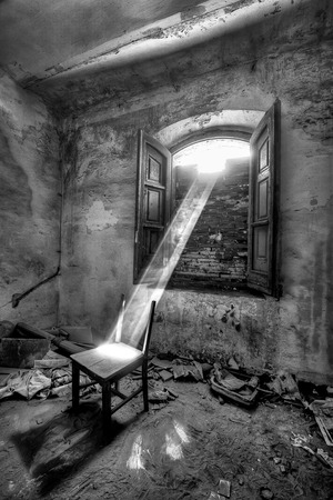 Interior of abondened building. A beam of sunlight shines through a boarded window upon an old chair