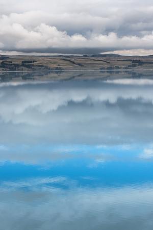 Land and sky reflected onto the water of Lake Tekapo, New Zealand.