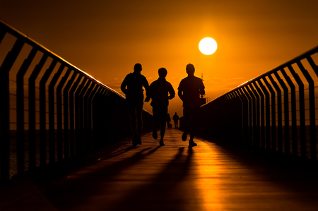 common goals: Backlit silhouette of three runners running towards the rising sun at the end of pier. Stock Photo