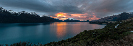 most: Panoramic view along the road from Queenstown to Glenorchy overlooking Lake Wakitipu and surrounding snow-capped mountains at sunset, New Zealand. Stock Photo