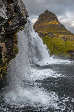 Kirkjufell, 463 m. high mountain on the north coast of Icelands Snaefellsnes peninsula, seen from the base of the near by waterfall.