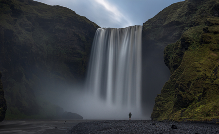 mesmerized: A man stands in awe infront of the magnificent waterfall of Skogafoss, Iceland