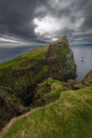 View over the northern tip of the island of Mykines with its white lighthouse in the distance, Faroe Islands
