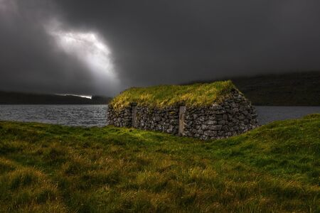 sod: Turf roof stone dwelling situated on the shore of the sea, Faroe Islands