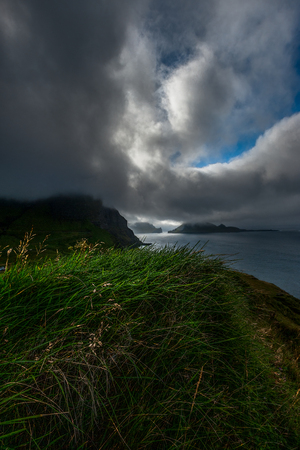 View from over the top of a green grassy hill towards the ocean and islets under a overcast blue sky with clouds, Faroe Islands.