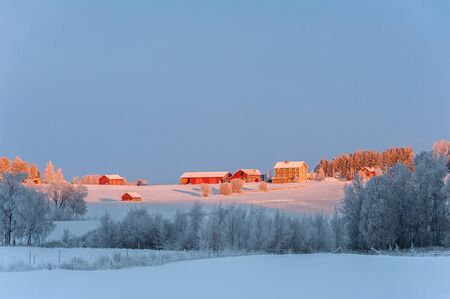 Typical red, wooden farm-houses set in the snowy countryside of northern Sweden. Stok Fotoğraf