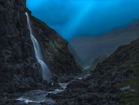 Lichtbalk over waterval in kleine vallei bij avondval, Faeröer. Stockfoto