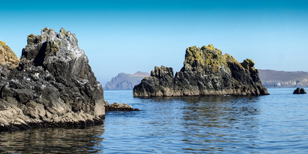 Rocks with Blasket Island in the background and a clear blue sky near Slea Head on the Dingle peninsula in Ireland