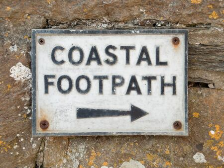 quin: Coastal footpath sign on a stone wall in Port Quin in Cornwall, England, UK Stock Photo