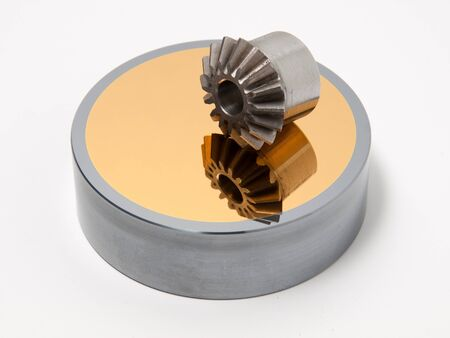 bevel: Bevel gear-wheel on a golden mirror isolated against a white background