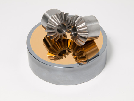 bevel: Bevel gear-wheels on a golden mirror isolated against a white background