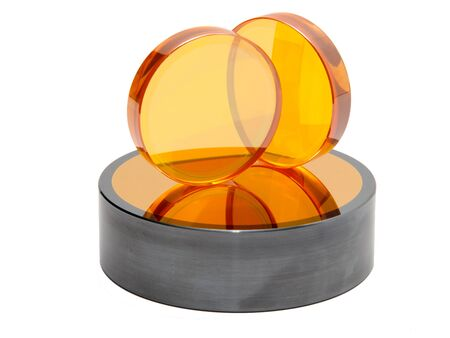 tilted: Orange lenses with tilted mirror needed as spare parts in a laser cutting device Stock Photo