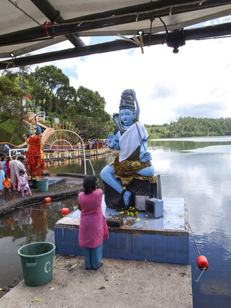 hindu god shiva: GRAND BASSIN, MAURITIUS - FEBRUARY 24, 2011: Woman prays before the Statue of the Hindu god Shiva during the Hindu festival of Maha Shivaratri in Mauritius.