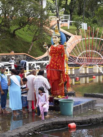 sacra famiglia: Grand Bassin, Mauritius - 24 febbraio 2011: Statua della dea ind� Laksmi con la preghiera dei pellegrini durante la festa ind� di Maha Shivaratri a Mauritius. Editoriali