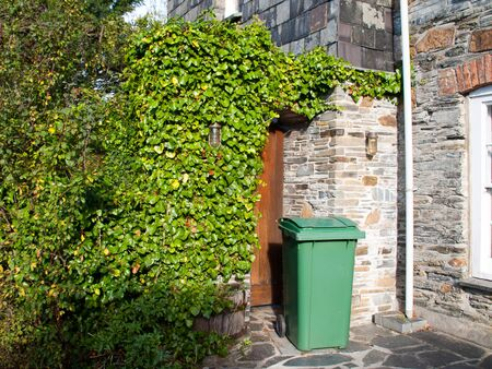 wheelie bin: Green wheelie bin in front of a house entrance somewhere in Port Isaac in north Cornwall