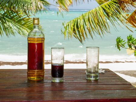 alcoholic beverage: Drink with rum and cola at the beach of Roche Noir in Mauritius Stock Photo