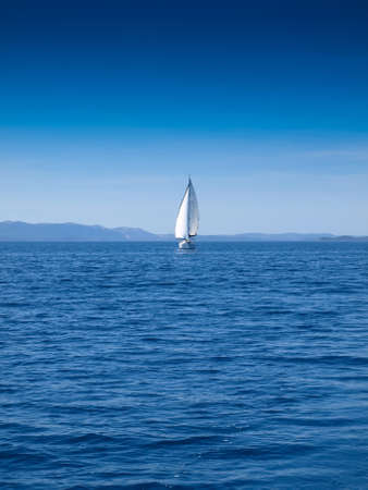 deportes nauticos: Front view of a sailing boat in an open blue sea and a clear blue sky