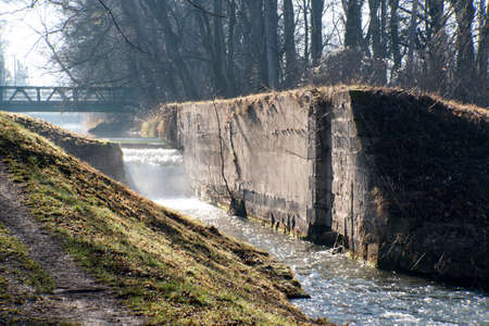 canal lock: Abandoned and ruined canal lock on the Wiener Neustaedter Kanal in Austria with a spraying waterfall against the light.