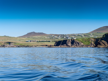 dunquin: View to Dunquin from a fishing boat near the Slea Head on the Dingle Peninsula in Ireland with a clear deep blue sky Stock Photo