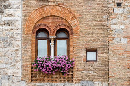 Ancient window with flowers in the medieval town San Gimignano in Tuscany, Italy. Stock Photo
