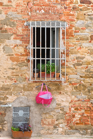 iron barred: Barred window with a pink shopping bag hanging on the grid. Picture taken on a public street in the historic village Sinalunga in tuscany, Italy.