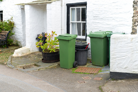 wheelie: Green and black wheelie bins in front of a house entrance somewhere in the picturesque  fishing village Port Isaac in north Cornwall. Picture taken from a public street. Stock Photo