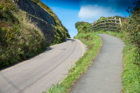 Part of the single track connecting road with a footpath between Port Isaac and Port Gaverne in northern Cornwall. Stock Photo