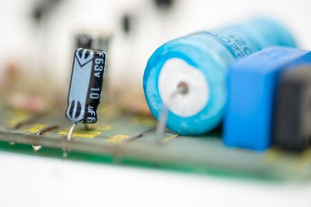 electrolytic: Closeup of two electrolytic capacitors on a vintage circuit board for a signal generator from the 1970th. Stock Photo